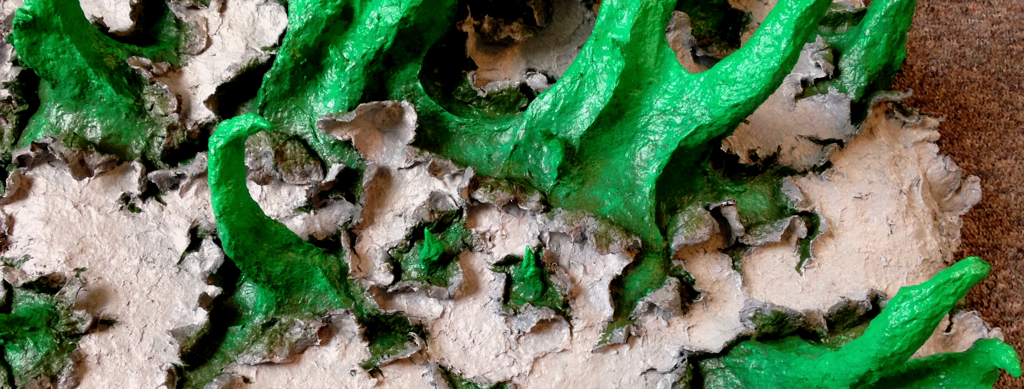 Detail of a sculpture in progress by MJ Seal made from paper mache that resembles spiky, spring green tentacles breaking out of a gray, papery skin