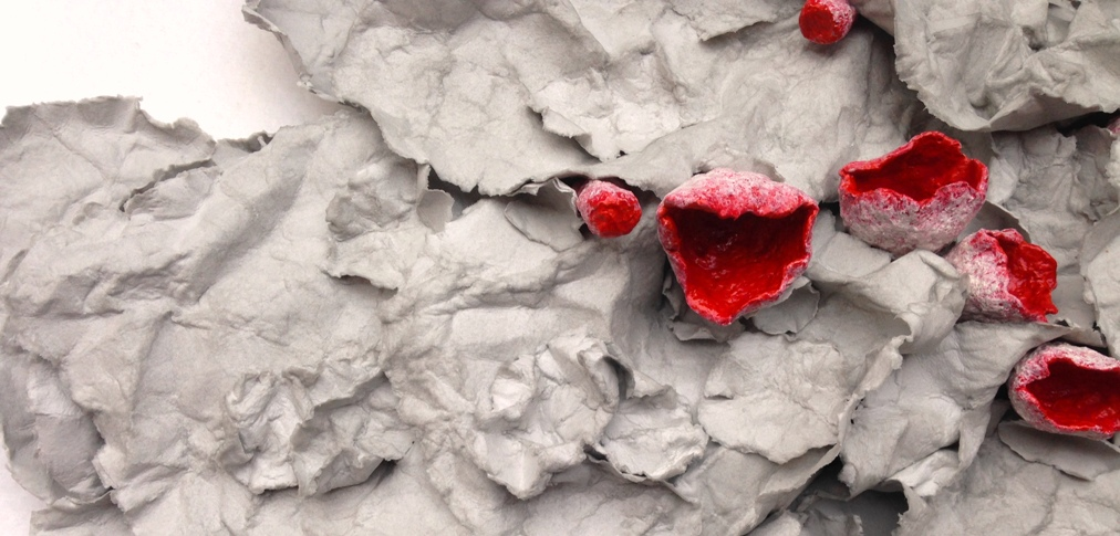 A paper mache sculpture by MJ Seal that resembles a cluster of Scarlet Cup Fungus emerging from a pile of dried, gray leaves