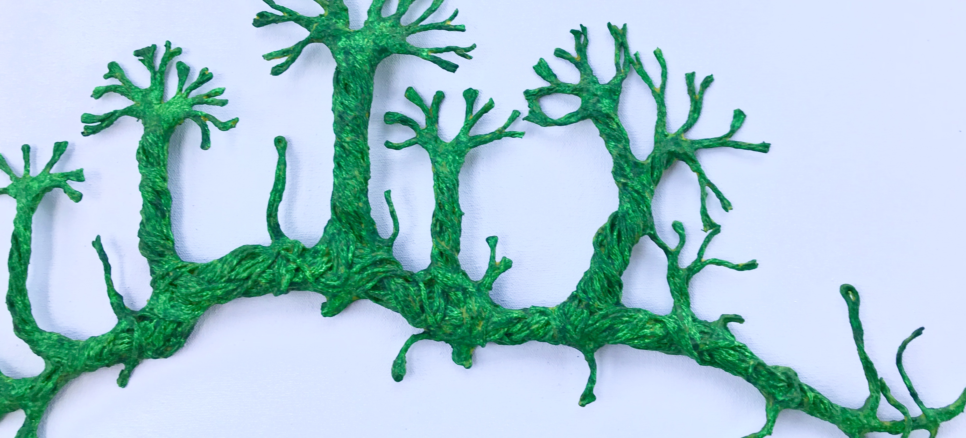 Detail of an original sculpture by MJ Seal made from thread and paper mache that resembles some primitive, emerald green forest of vines
