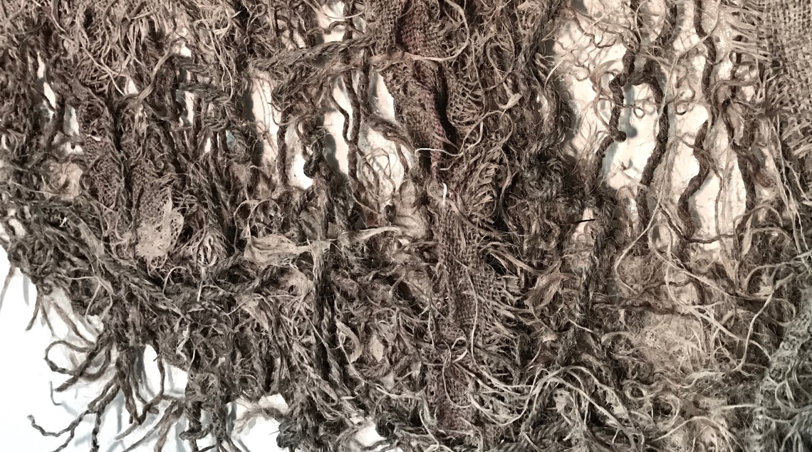Detail of an abstract forest of burlap scraps and twine