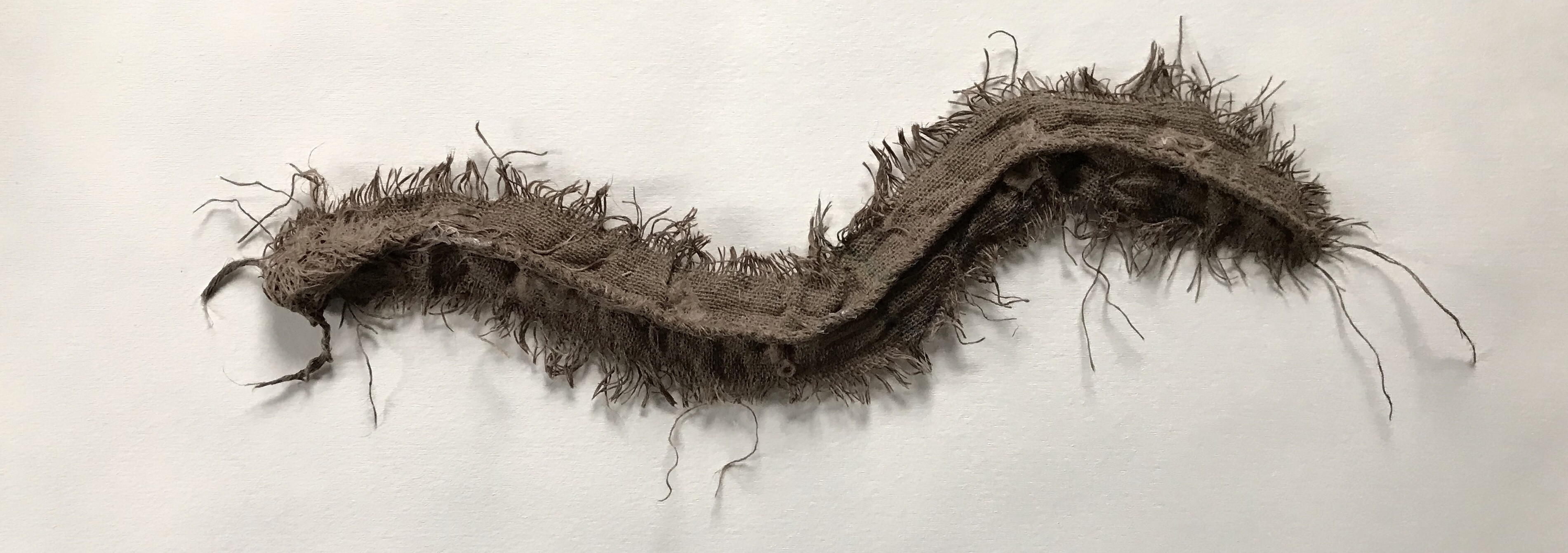 a fabric art piece made from sackcloth that resembles a giant centipede
