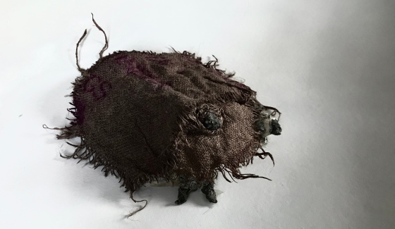 front view of a sculpture in progress by MJ Seal made from ashes, mildewy bible pages and sackcloth that resembles a monstrous primitive insect