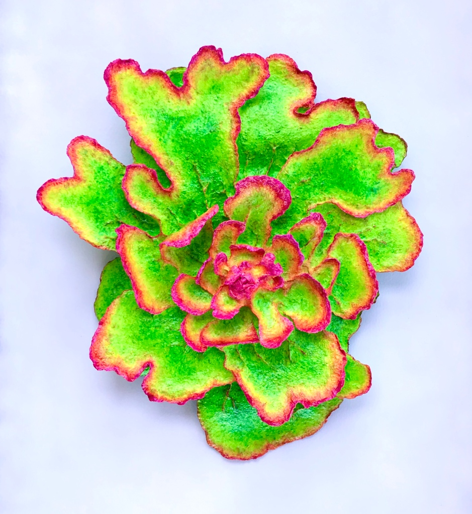 full view of An abstract paper mache sculpture by MJ Seal that resembles a psychedelic lichen or flower in hues of chartreuse and magenta