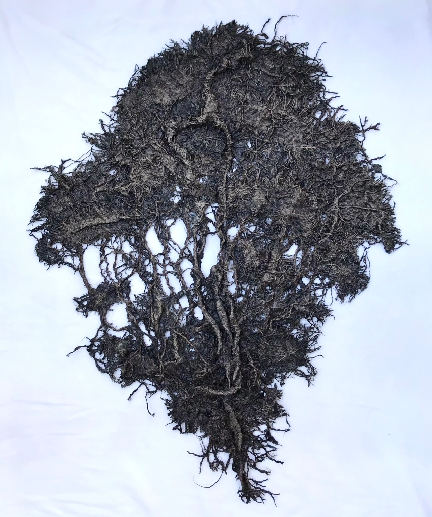 Full view of an abstract fabric sculpture by MJ Seal that resembles a giant, dark gray sea fan