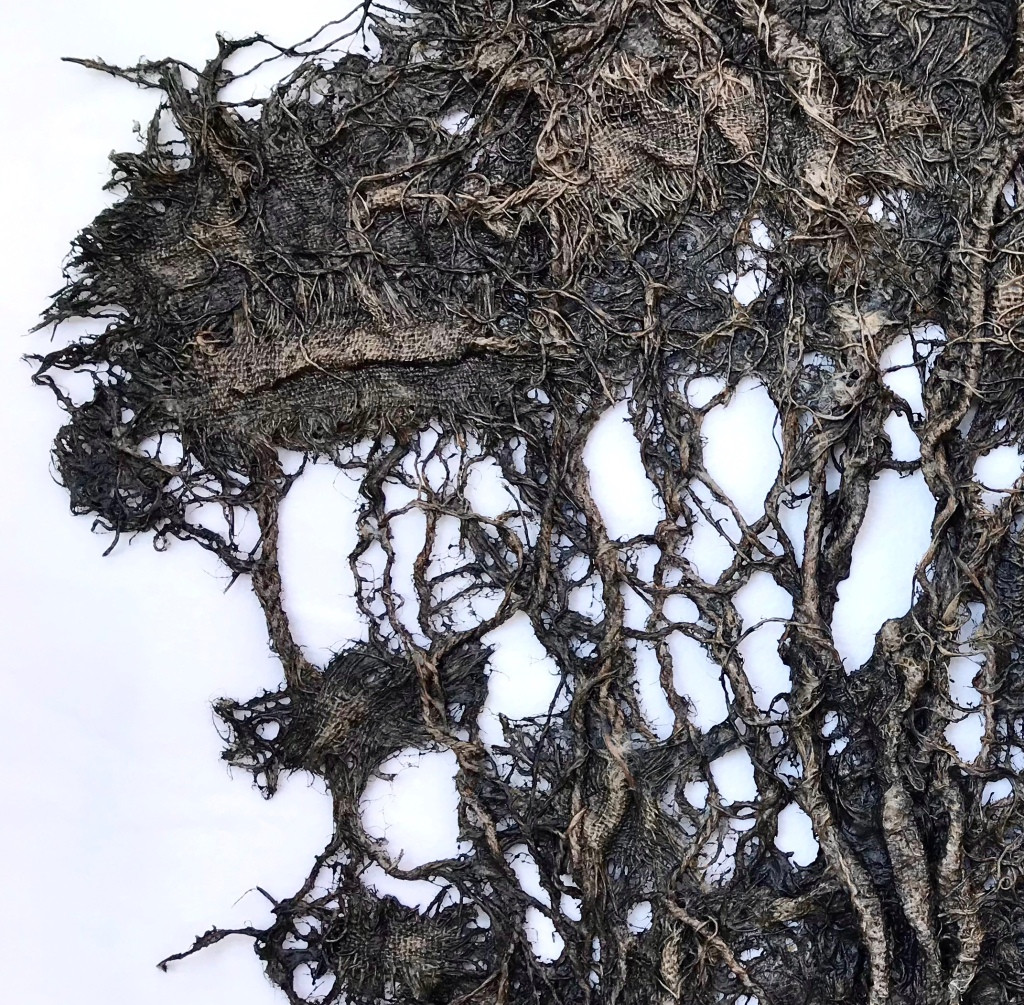 Detail of an abstract fabric sculpture by MJ Seal that resembles a giant, dark gray sea fan