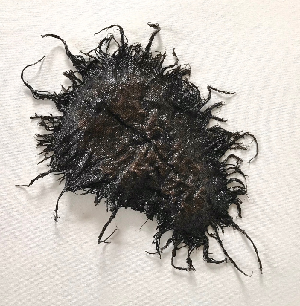 Full view of an abstract sculpture made from sackcloth by MJ Seal that resembles a giant, glistening, blackish brown sea scorpion