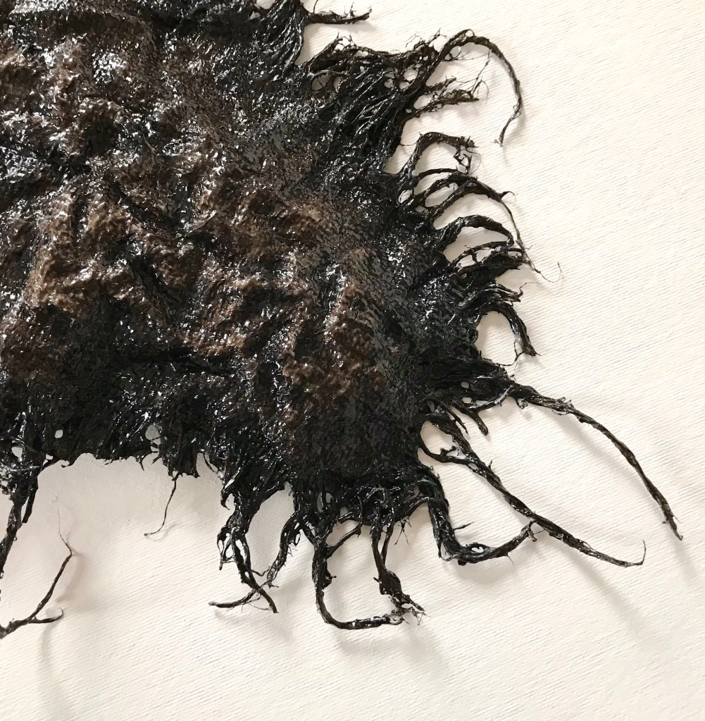 Detail of an abstract sculpture made from sackcloth by MJ Seal that resembles a giant, glistening, blackish brown sea scorpion