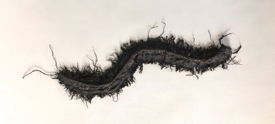 Full view of an abstract sculpture made from sackcloth by MJ Seal that resembles a giant, glistening, blackish brown centipede