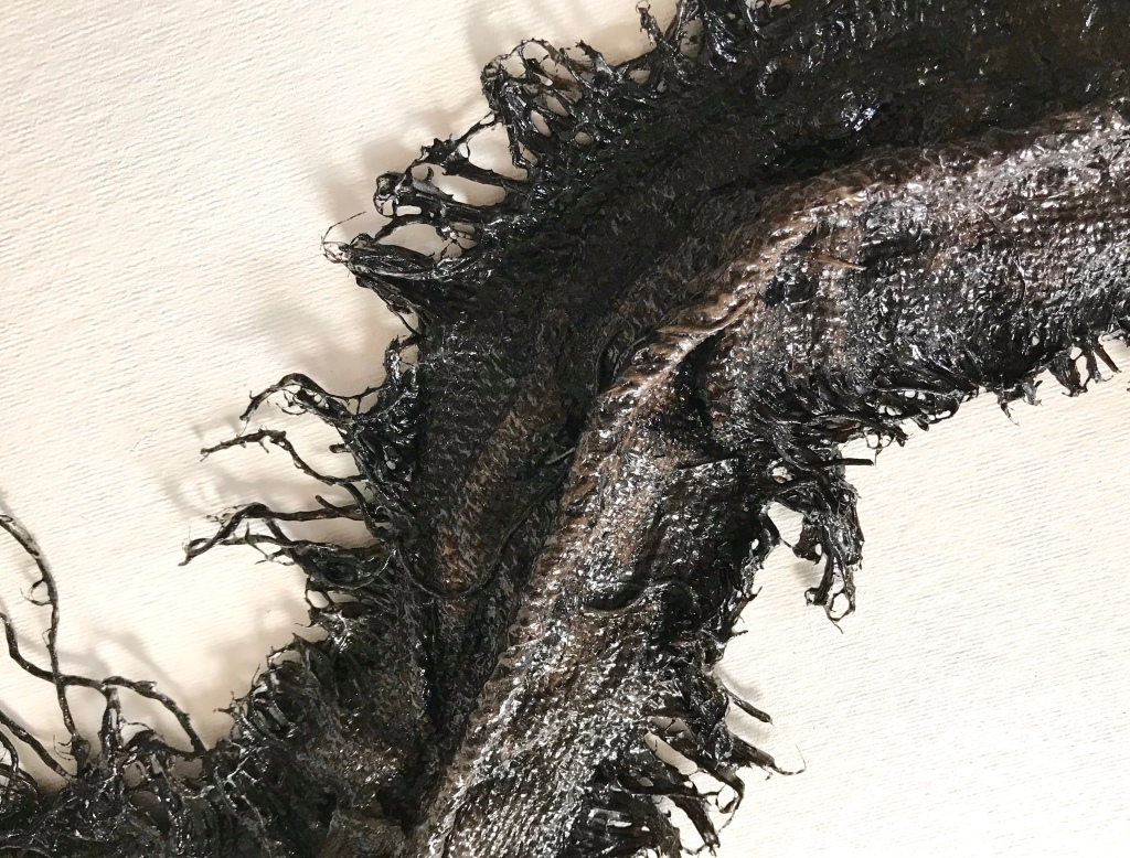 Detail of an abstract sculpture made from sackcloth by MJ Seal that resembles a giant, glistening, blackish brown centipede