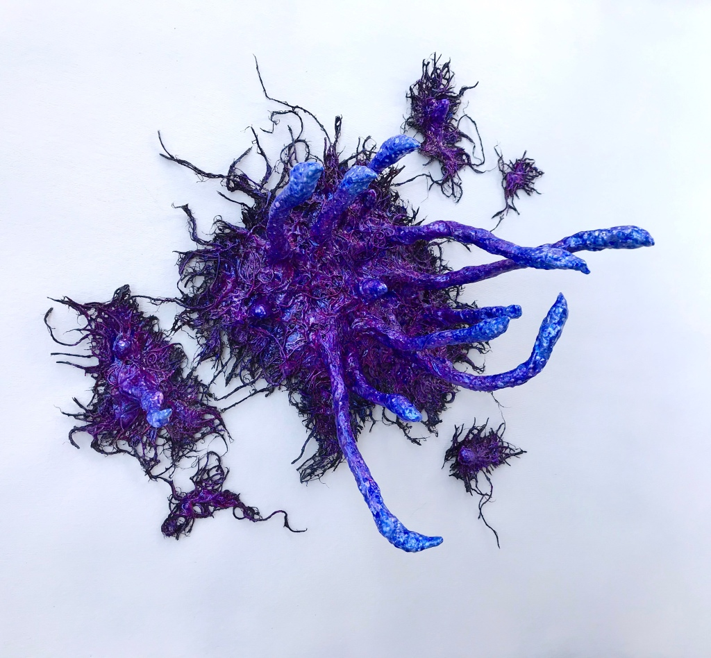 Full view of an abstract paper mache sculpture by MJ Seal that resembles an iridescent octopus reaching through a wall