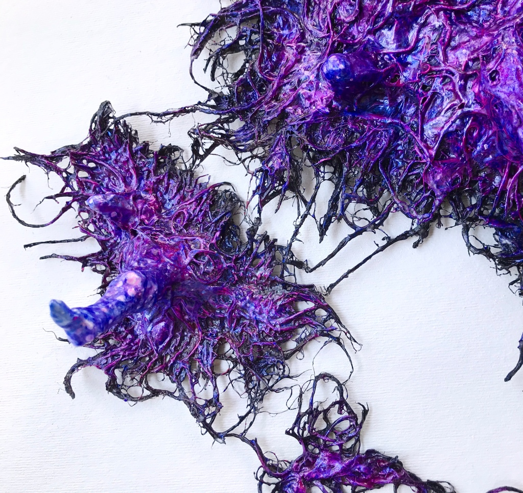 Detail of an abstract paper mache sculpture by MJ Seal that resembles an iridescent octopus reaching through a wall