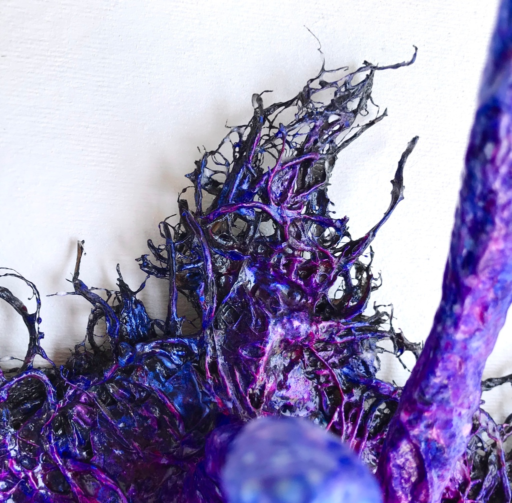 Detail of an abstract paper mache sculpture by MJ Seal that resembles an iridescent octopus reaching through a wall