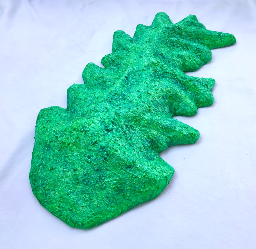 Full view of an abstract paper mache by MJ Seal that resembles a cross between a mountain and a primitive sea creature with green reptilian skin