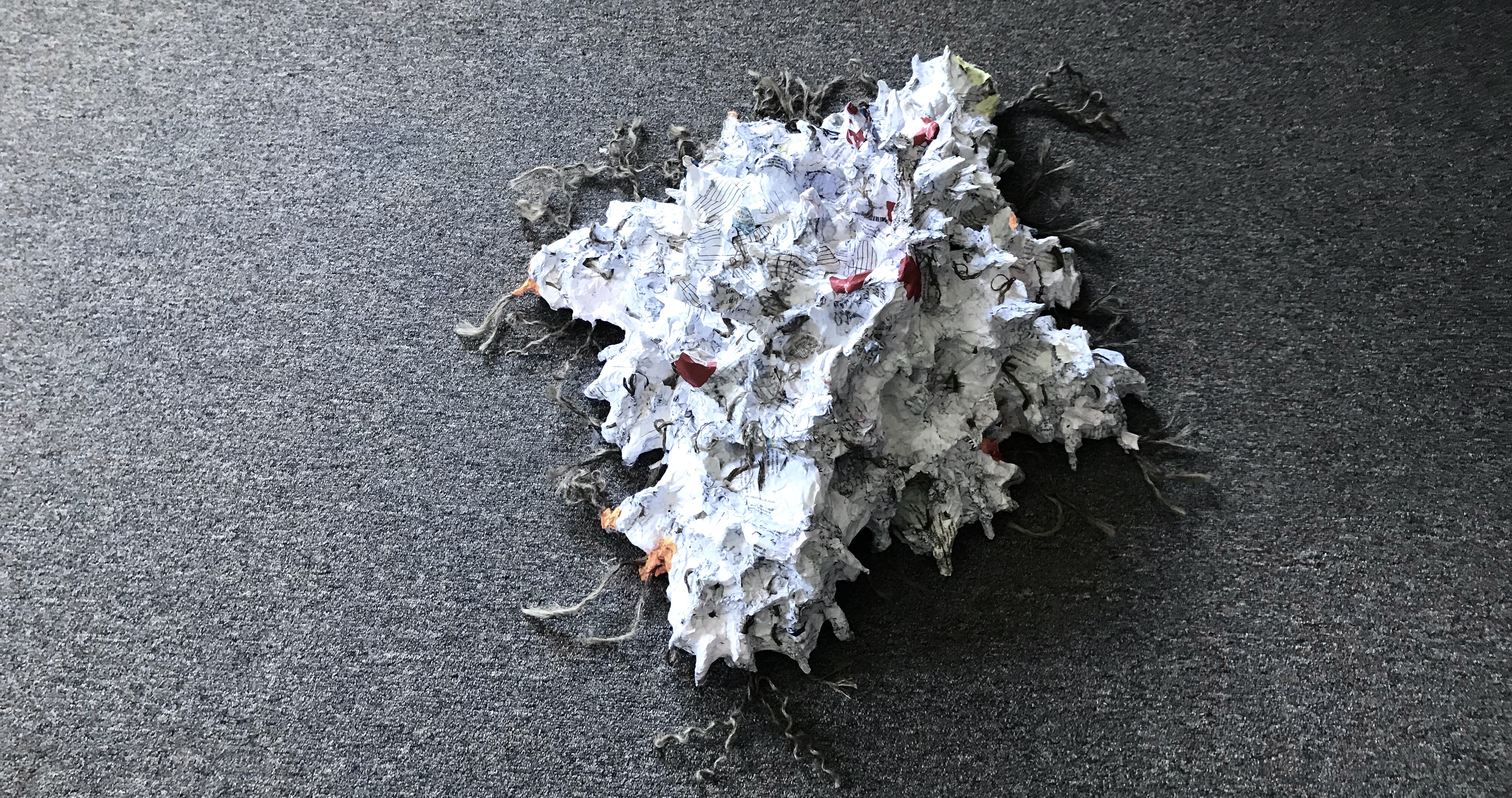Dorsal view of an abstract paper mache sculpture in progress by MJ Seal that resembles a peculiar starfish or some strange, compass rose shaped temple with multitudes of faces