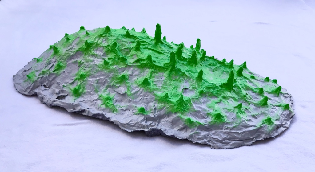 One of five pieces of an abstract paper mache sculpture by MJ Seal that resmbles a group of giant gray slugs with acid green spikes roving across the ground