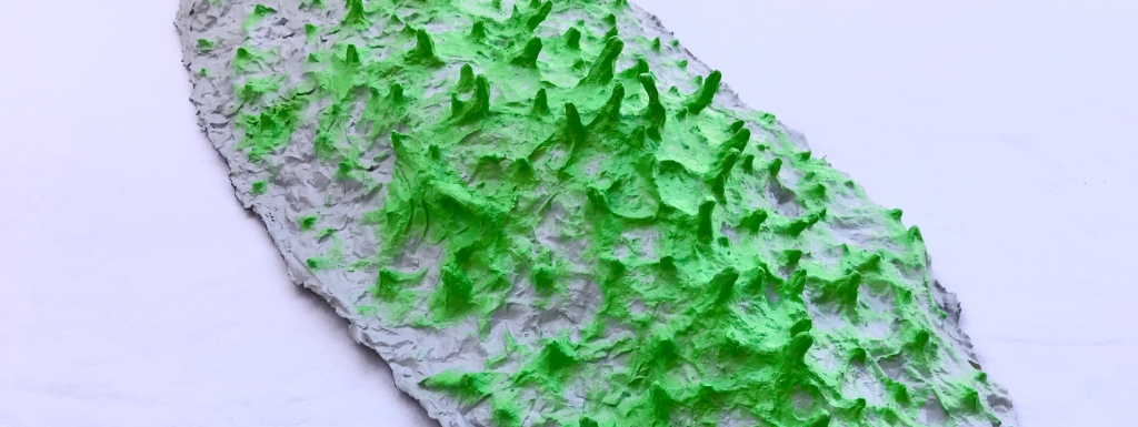Close up detail of one of the five pieces of an abstract paper mache sculpture by MJ Seal that resmbles a group of giant gray slugs with acid green spikes roving across the ground