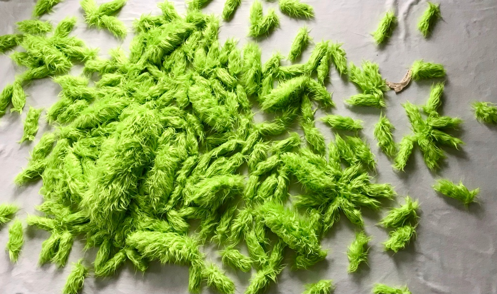 overhead view of a large fabric art installation piece by MJ Seal made from chartreuse green faux flokati fabric that resembles a swarm of giant acid green caterpillars