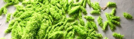 Detail of a large fabric art installation piece by MJ Seal made from chartreuse green faux flokati fabric that resembles a swarm of giant acid green caterpillars